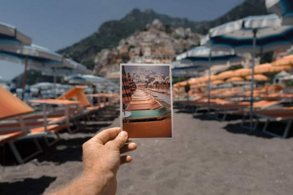 man at a beach, holding photo of the same beach